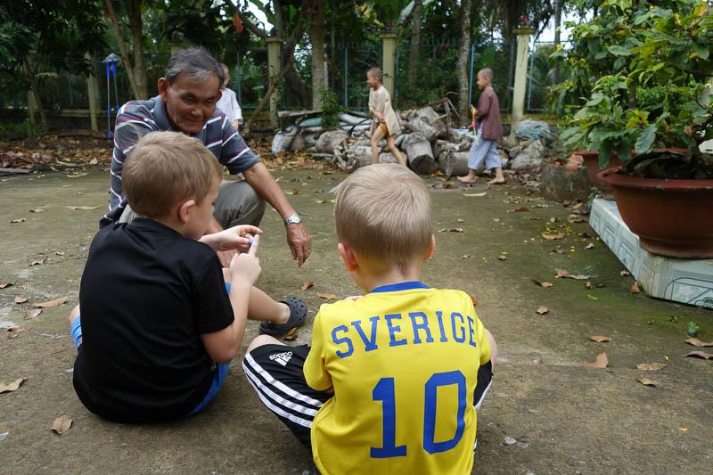 Grabbarna lär sig spela kula på klassiskt vietnamvis.